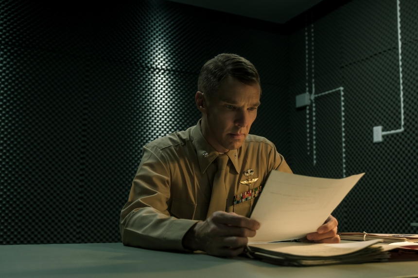 A soldier is sat in a dark room looking intensely at a piece of paper.