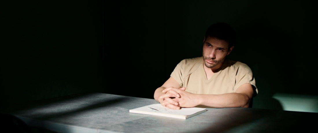 Image is from the film 'The Mauritanian'. A prisoner sits in a dark interrogation room with his hands clasped.