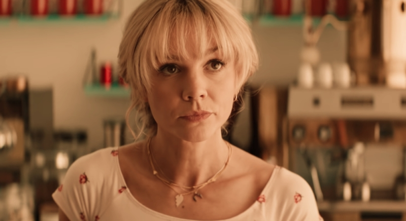 Image is from the film 'Promising Young Woman'. Cassie (Carey Mulligan) stands behind a coffee counter. She appears to be looking at someone.