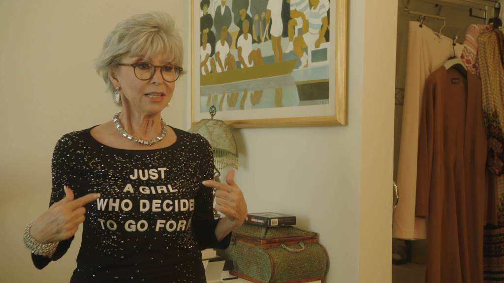 """Rita Moreno points to her bedazzled shirt that reads """"Just a Girl Who Decided to Go for It"""""""