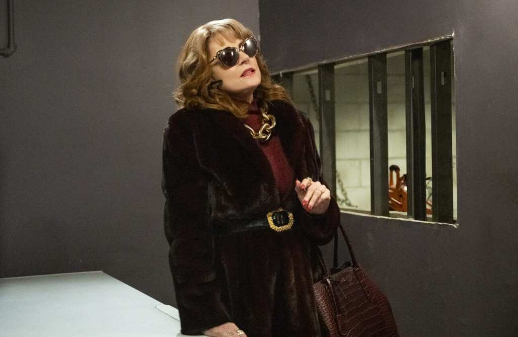 A woman wearing a fur coat and sunglasses indoors is standing in what appears to be a basement.