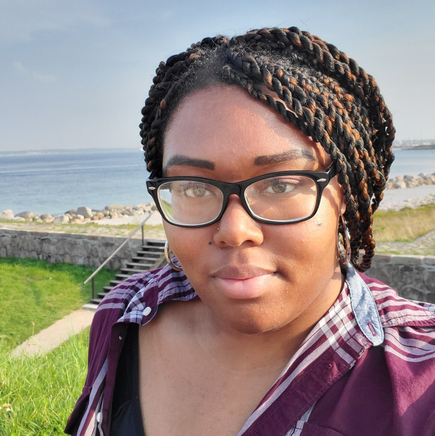 A selfie of Shania Russell, who smiles at the camera with the sea in the background.