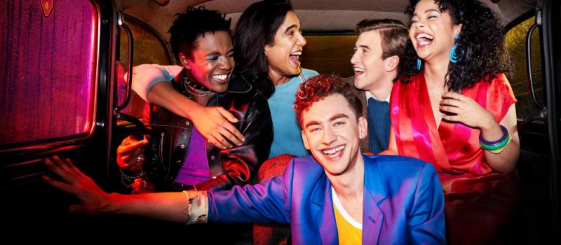 The cast of It's a Sin sit in the back of a taxi wearing brightly coloured clothing and laughing or smiling.