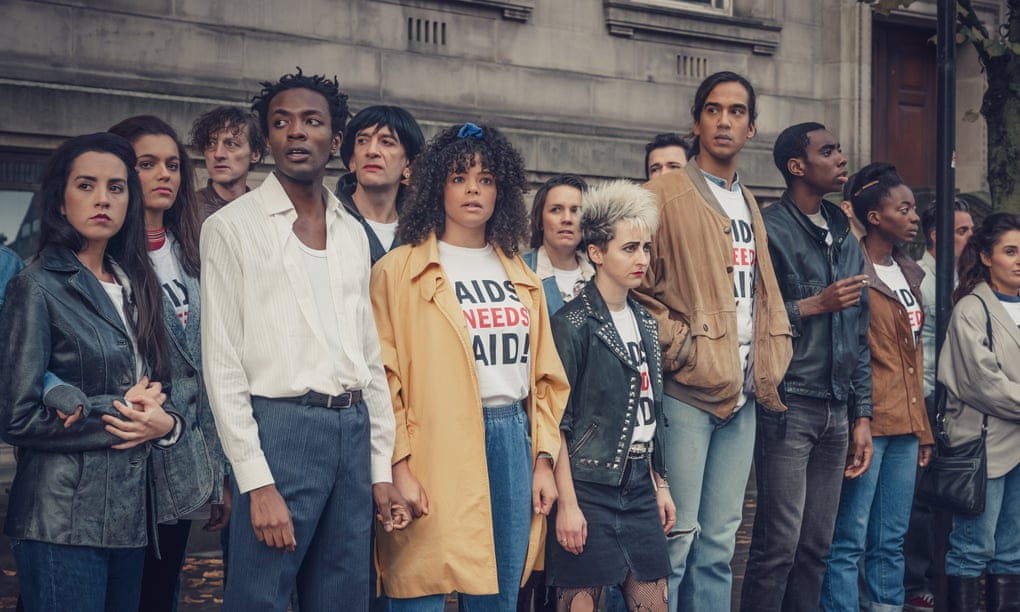 Lydia and Roscoe nervously stand with a group of their friends at a protest wearing 'AIDS need aid' t-shirts.