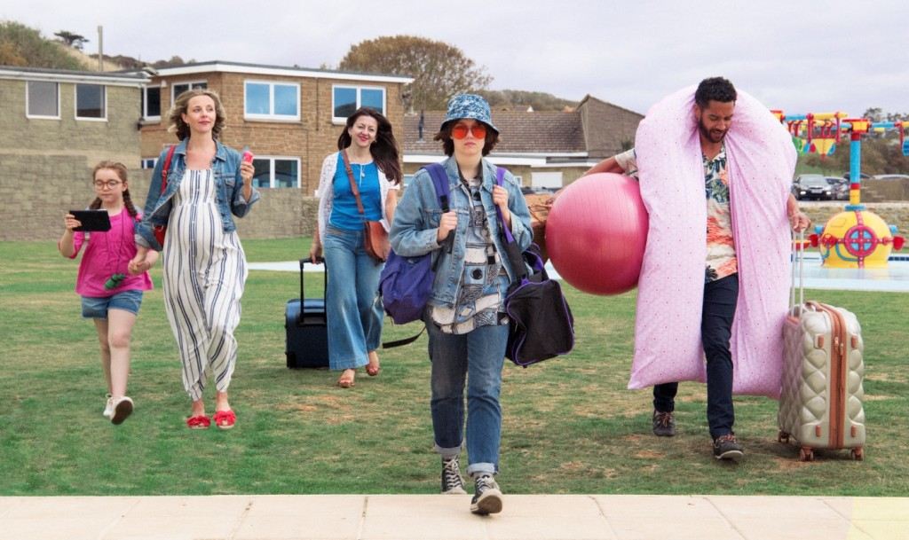 A family of characters walk towards the screen, all carrying suitcases and holiday essentials. A young girl is glued to her tablet, holding the hand of a pregnant woman. Behind them, a woman smiles holding a suitcase. Next to them, a young woman dressed in androgynous clothing walks in strides. On the end, a man holds a yoga ball and a suitcase, with a pregnancy pillow wrapped around his neck.