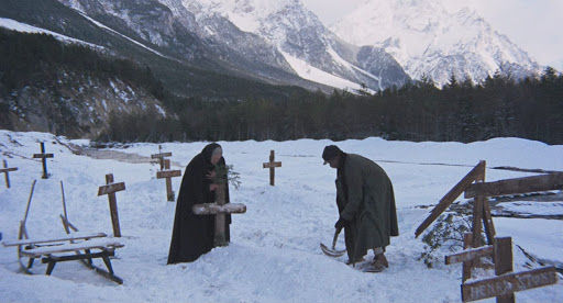 Two elderly people borrow a fresh grave in the snow with a white landscape towering behind them.