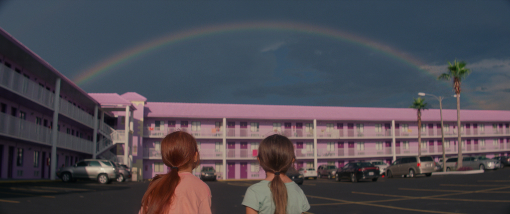 A still from 'The Florida Project.' Two young girls look at a rainbow over a pastel purple motel.