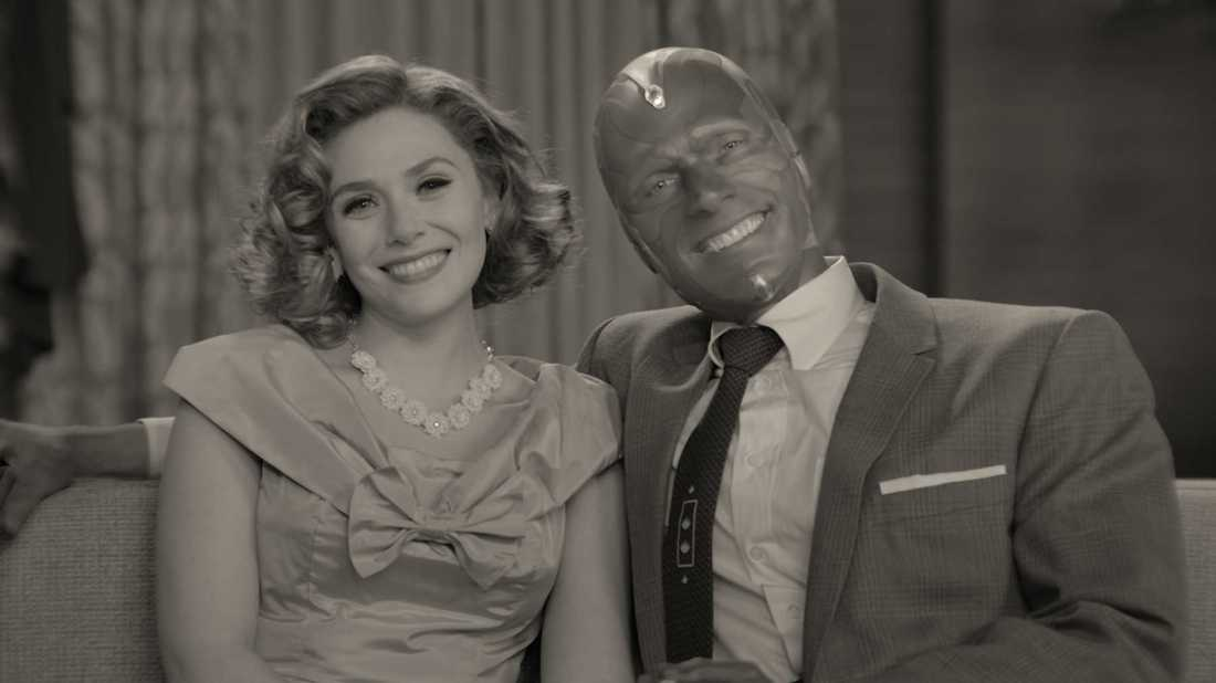 Image from the TV Series 'WandaVision'. Wanda and Vision sit side by side on a couch, both smiling at the camera. Wanda is wearing a dress with a large bow at the front and Vision a suit. The image is in black and white.