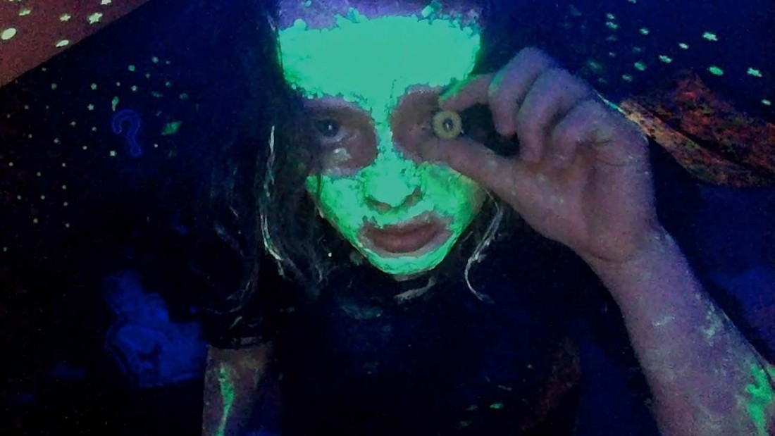 Anna Cobb stares at the camera, covered in glow in the dark paint