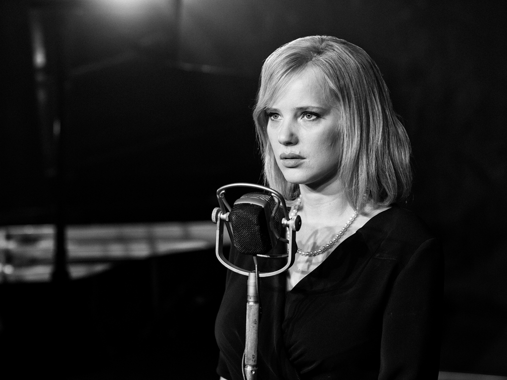 Zula, wearing a black dress and a white pearl necklace, stands in front of the microphone. The image is in black and white.