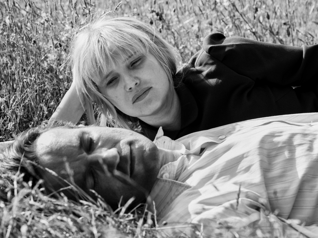 Wiktor and Zula lay in a field. Zula lays on her side and watches him. He is wearing a white shirt with stripes whilst she wears black. The image is in black and white.