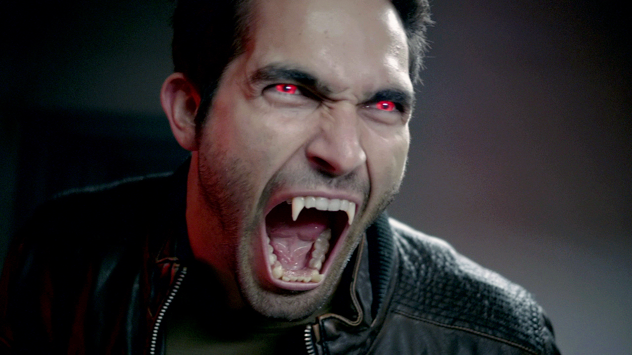 Image is from the TV Show 'Teen Wolf'. An adult male werewolf in human form bares his pointed teeth. His eyes are glowing red and he is also wearing a leather jacket.