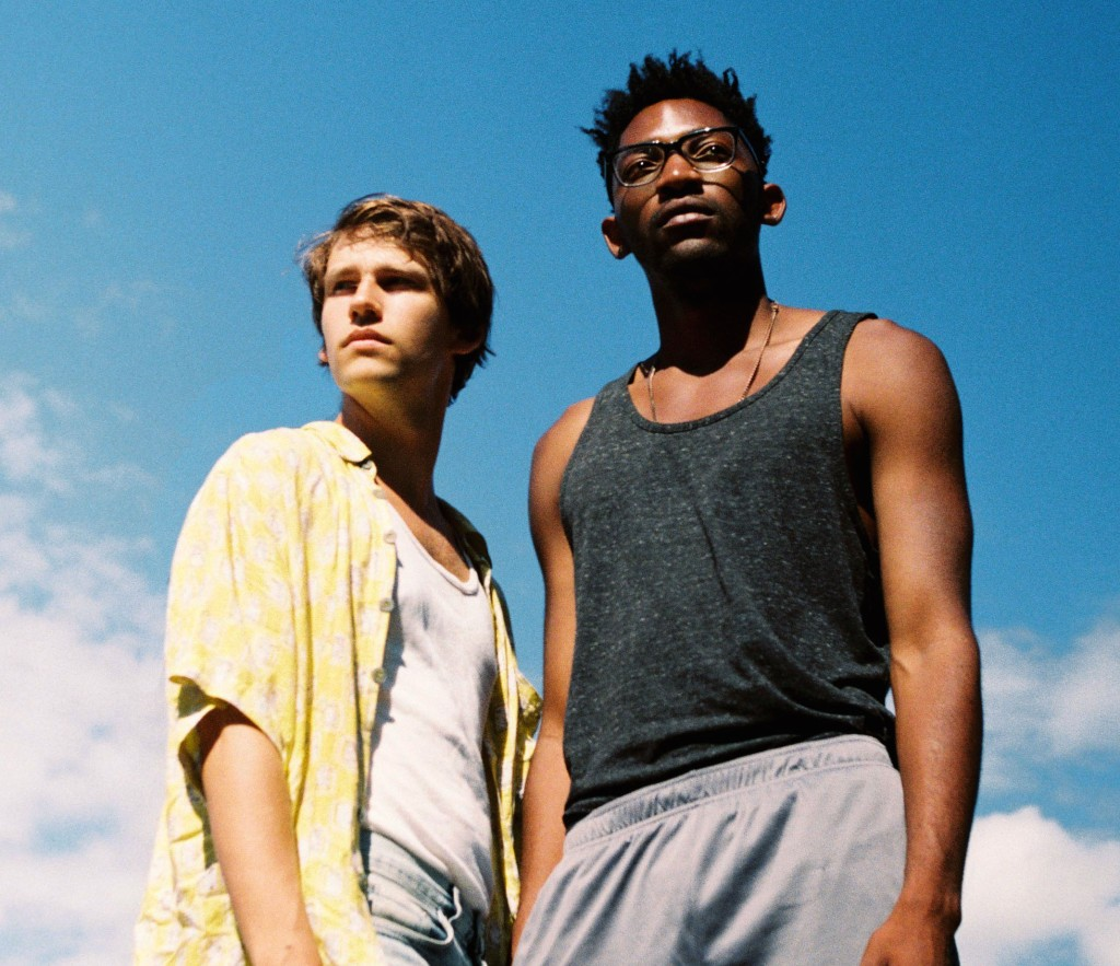 Image is from the film 'Boy Meets Boy' (2021). Two boys stand beside one another, looking out into the horizon. One is wearing a yellow shirt, the other a grey tank top.