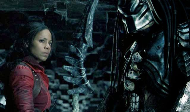 Sanaa Lathan as Alexa Woods in Alien vs. Predator (2004). Alexa is wearing a red jacket and is looking into the distance. Next to her, stands a large, masked figure.