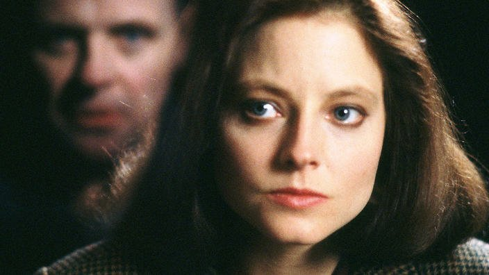 Image is from the film 'The Silence of the Lambs' (1991). Clarice looks seriously and earnestly at the devilish face of Hannibal, reflected imposingly for the audience in the glass