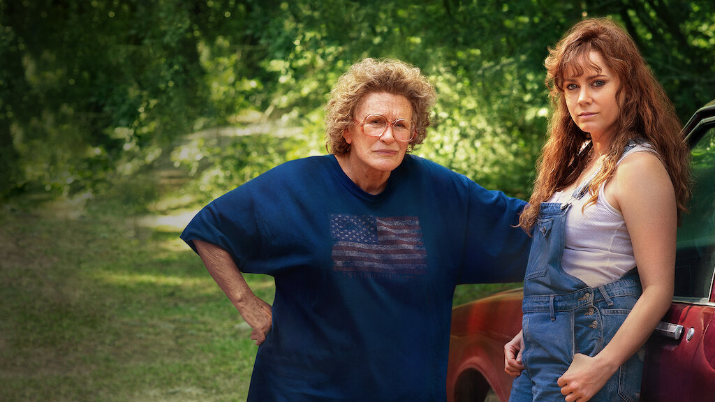 Film still from the film Hillbilly Elegy. Amy Adams leans against a red car wearing dungarees and glenn Close is behind her, hand against the car, wearing a worn American flag T-Shirt.