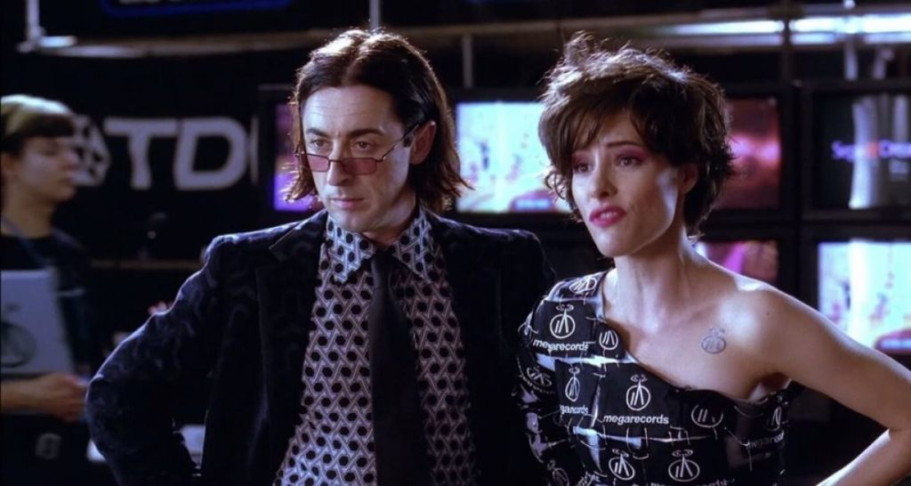 Alan Cumming (white, brown hair cut in a bob parted down the middle) stands next to Parker Posey (white, short wavy hair), both give a judgemental look to someone off camera.