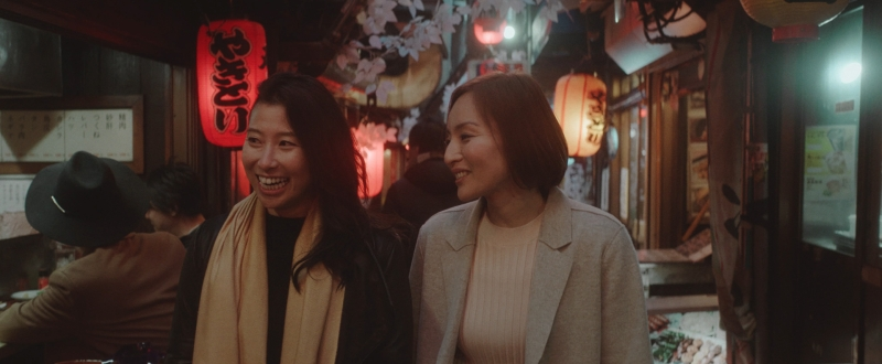 Image is from the short film 'And Then' (2021). Two woman walk side by side in a Japanese market street. They appear to be chatting.
