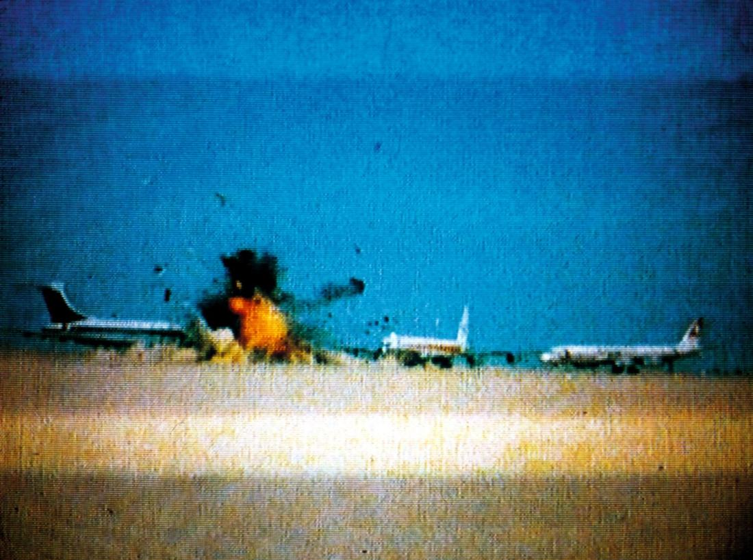 Image is from the documentary 'Dial H-I-S-T-O-R-Y' (1997). Image shows grainy footage of a plane in the middle distance exploding on a landing strip.
