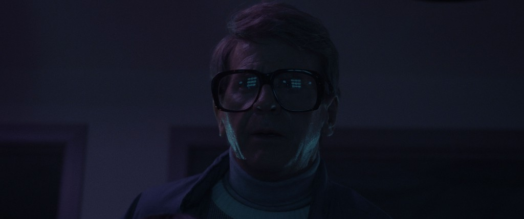 A mature man with large, thick-rimmed glasses gazes upon a CRT monitor that is out of the frame but reflected in the glasses. The CRT displays lines of text we can't read. The room is too dark to see the background but the man is slightly lit by blue, purple hues.