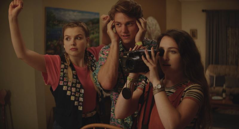 Image is from the film 'Dramarama' (2021). Three teens pretend to be a part of a camera crew and record the action in front of them. In the back, a girl wearing a pink shirt and black waistcoast holds a pretend boom pole. In the middle, a boy in a green patterned shirt holds his hands over his ears, pretending to hold headphones. In from of them a girl in orange dungarees holds a real VHS camera to her eye.