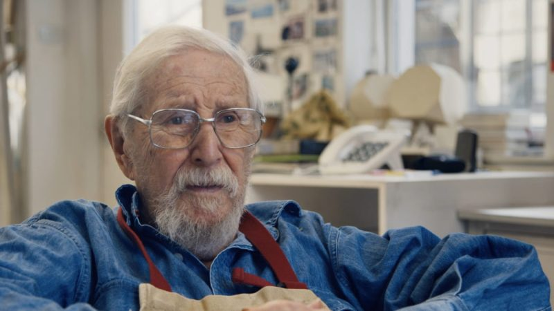 Image from the documentary 'Eye of the Storm' (2021). Eldery painter James Morrison sits in a close up, wearing an apron as he talks to someone behind the camera.