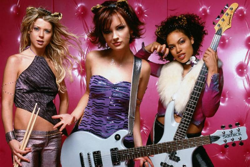 Band members Melody (white, wavy blonde hair with fuzzy cat ears, holding drumsticks), Josie (white, chin-length flippy auburn hair, furry cat ears, holding white guitar), and Valerie (Afrolatina, chin-length black curly hair, fuzzy cat ears, holding white bass guitar) stand in front of a tufted hot pink backdrop