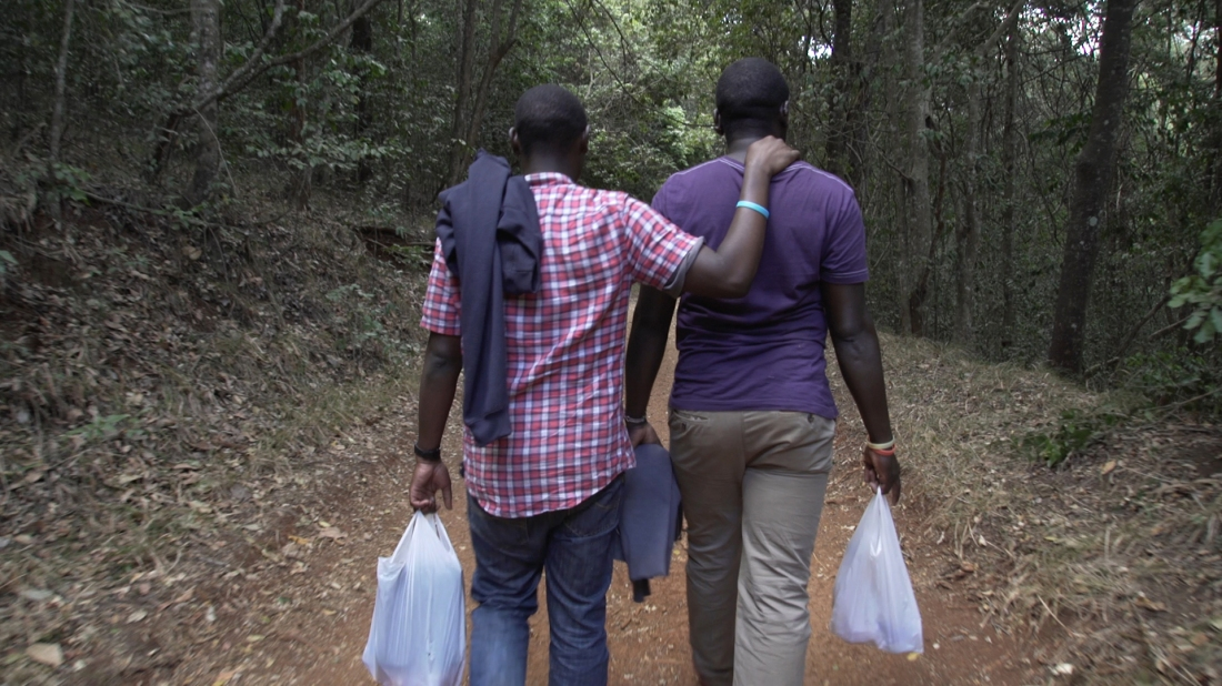 Image is from the documentary 'I Am Samuel' (2020). Two men walk side by side down a wooded path. Both are holding white plastic bags, with one of the men resting is arm on the others shoulder.