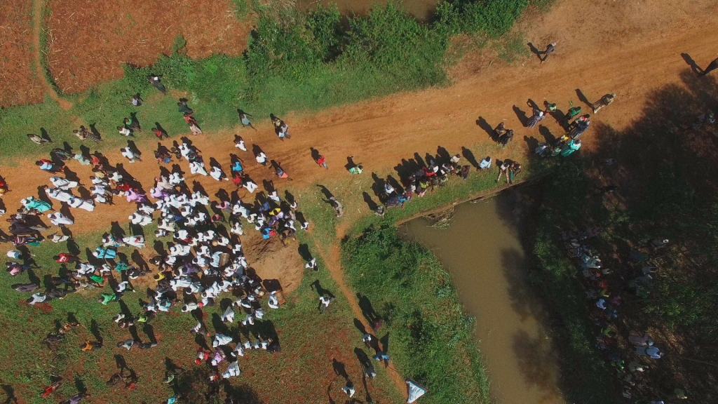 Image is an aerial shot of the Kenyan countryside, which sees large gatherings of people surrounding a muddy river.