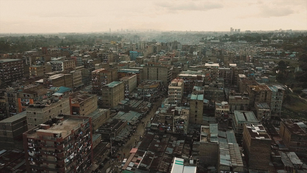 Image is an aerial shot of a Kenyan city on a dark and cloudy day.
