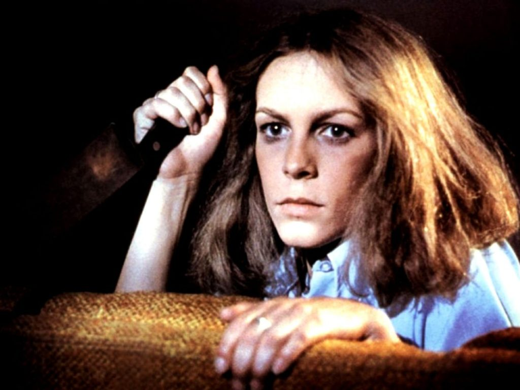 Jamie Lee Curtis as Laurie Strode in Halloween (1978). Laurie is holding a knife and is peering from behind a chair.