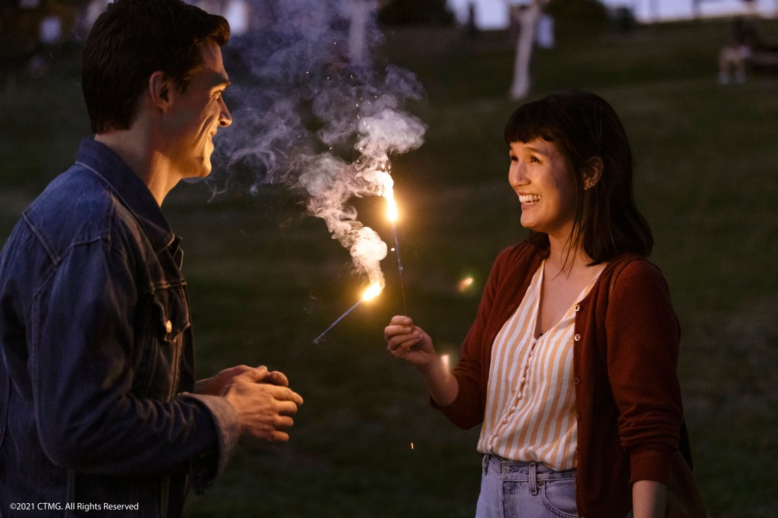 Image is from the film 'Long Weekend' (2021). A couple hold sparklers in the hands and laugh as they play with them in a darkening field.