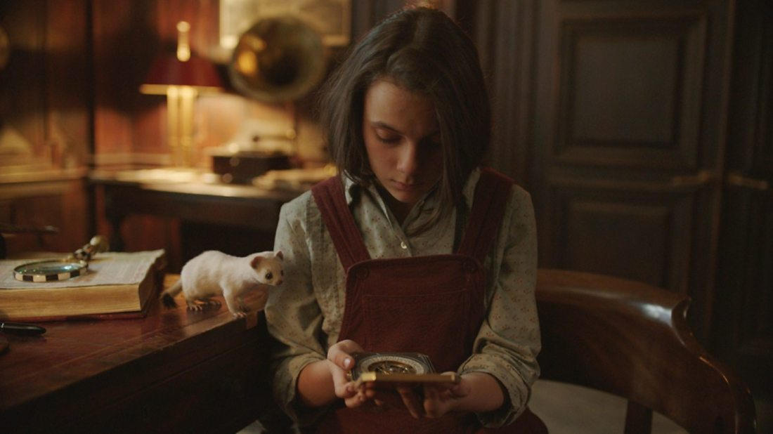 Image is from the TV Show 'His Dark Materials'. 'Lyra Belacqua (Dafne Keen), a brown haired white girl wearing a red pinafore, studies a golden compass she holds in her hand. She sits in an academic office and her daemon Pan stands curiously on the desk next to her, also looking thoughtfully at the compass. He is in the form of a white ermine.