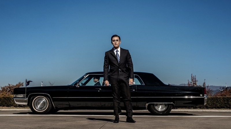 Image is from the film 'The Man Standing Next' (2021). A man in a suit stands in front of a sleek black car.