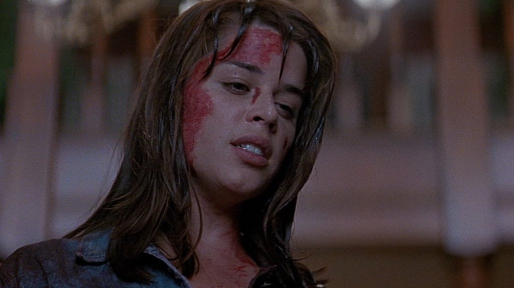 Neve Campbell as Sidney Prescott in Scream (1996.) She is looking down, the side of her head covered in blood.