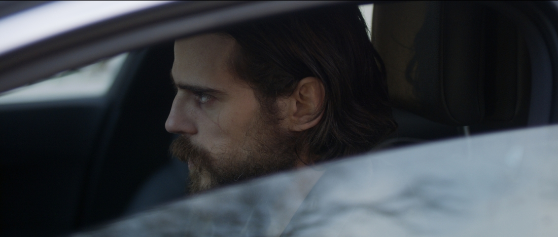 Image is from the film 'Out of This World'. A bearded man with long, dark hair looking broodingly at something. He is sat in a car.