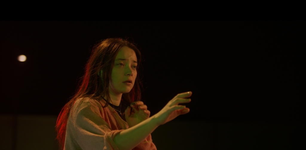 Image from the film 'Out of the World'. A young woman wearing a pink cardigan holds out her hand into the darkness. She is captivated by something.