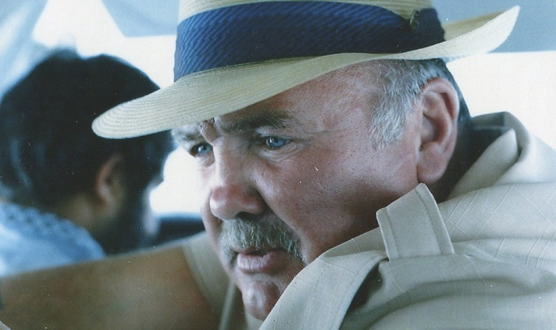 Image is from the film 'Killing Escobar' (2021). A man wearing a beige shirt and a straw hat sits in a car.