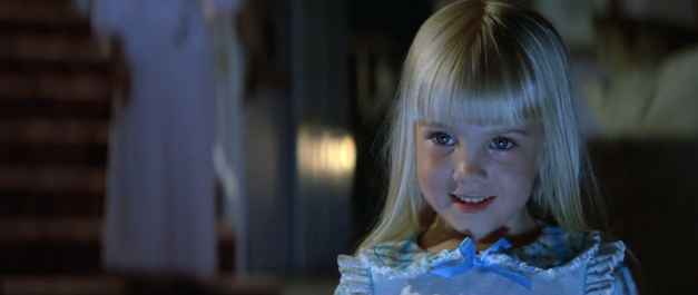 Heather O'Rourke as Carol Anne in Poltergeist. A young child with bright blonde hair and is wearing a blue nightdress smiles in a dimly lit hallway.