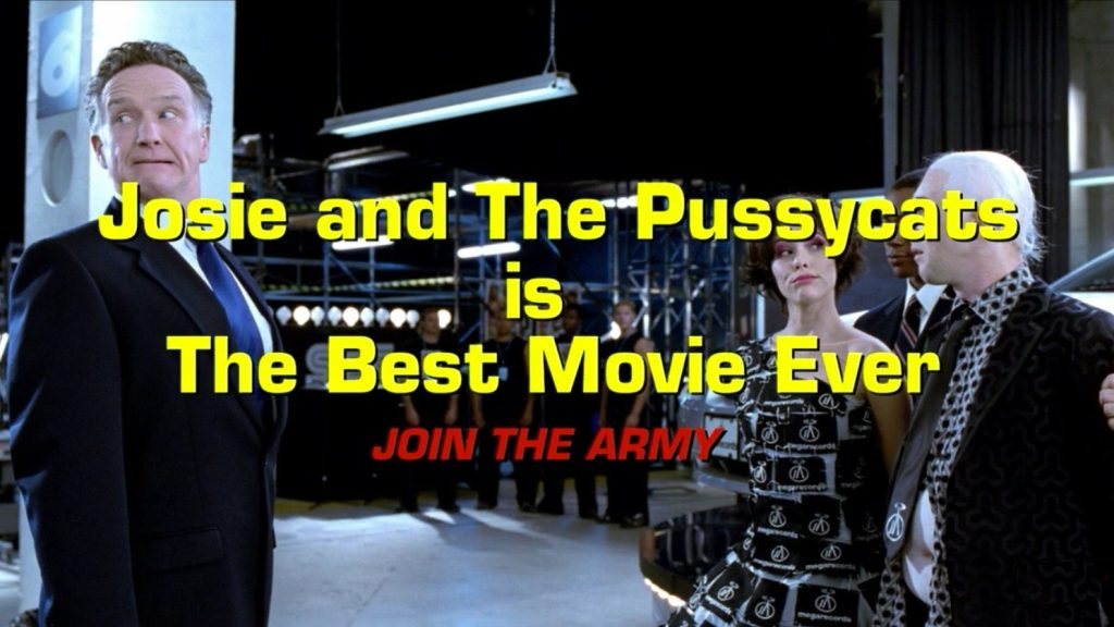 "Large yellow and red text that reads ""Josie and the Pussycats is The Best Movie Ever JOIN THE ARMY"" is set over an image of Parker Posey and Alan Cumming standing across from a white man in a suit"