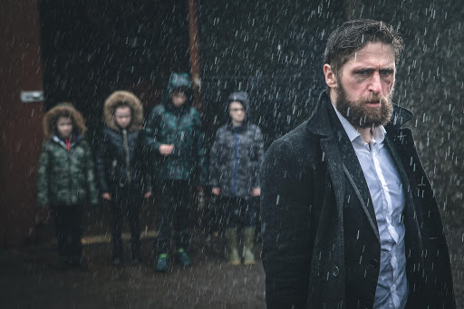 Image is from the film 'Redemption of a Rogue' (2021). A man wearing a black coat without a hood stands in the rain. Behind him stands four children who all are all wearing hooded coats.
