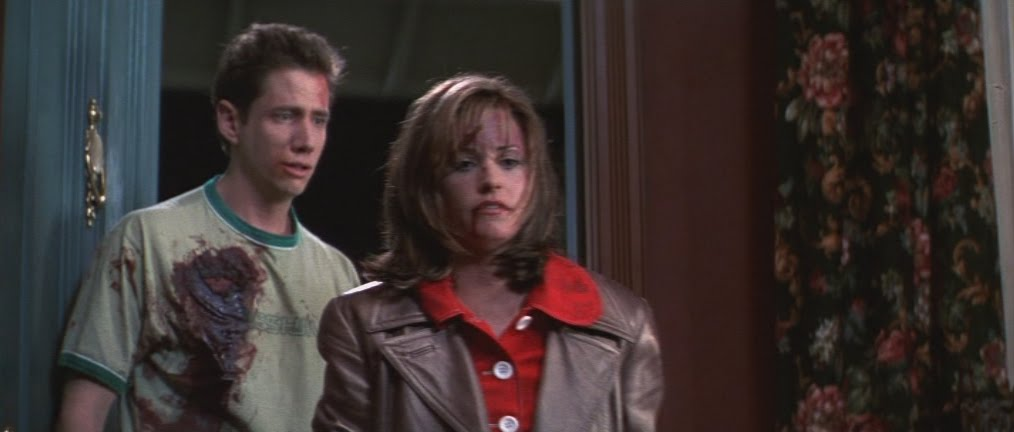 Courteney Cox as Gail Weathers and Jamie Kennedy as Randy Meeks in Scream (1996.) Gail looks down as she walks out of a house, a gash of blood on her lip and forehead. Behind her, Randy - who is also covered in blood - tries to stop her.