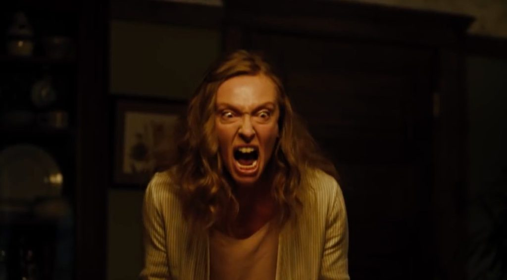 Toni Collette as Alice Graham in Hereditary (2018). Alice screams in a dimly lit room, where she is the only focus.