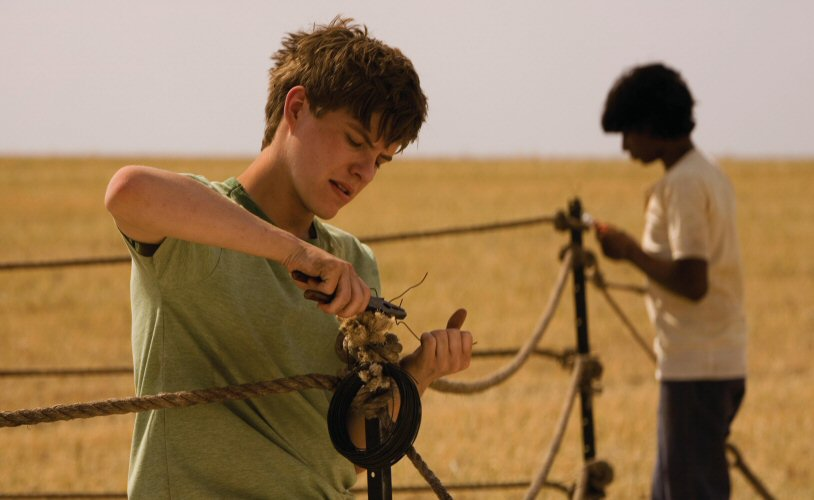 Image from the film September (2007). Ed (left) and Paddy (right) set up their boxing ring using rope, metal rods and wire in a corn field.