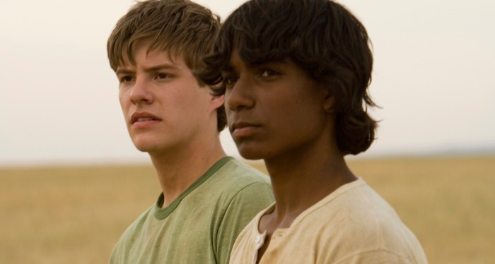 Image is from the film 'September' (2007). Two young boys stand in a field and look out into the distance. One is white, the other is aboriginal Australian.