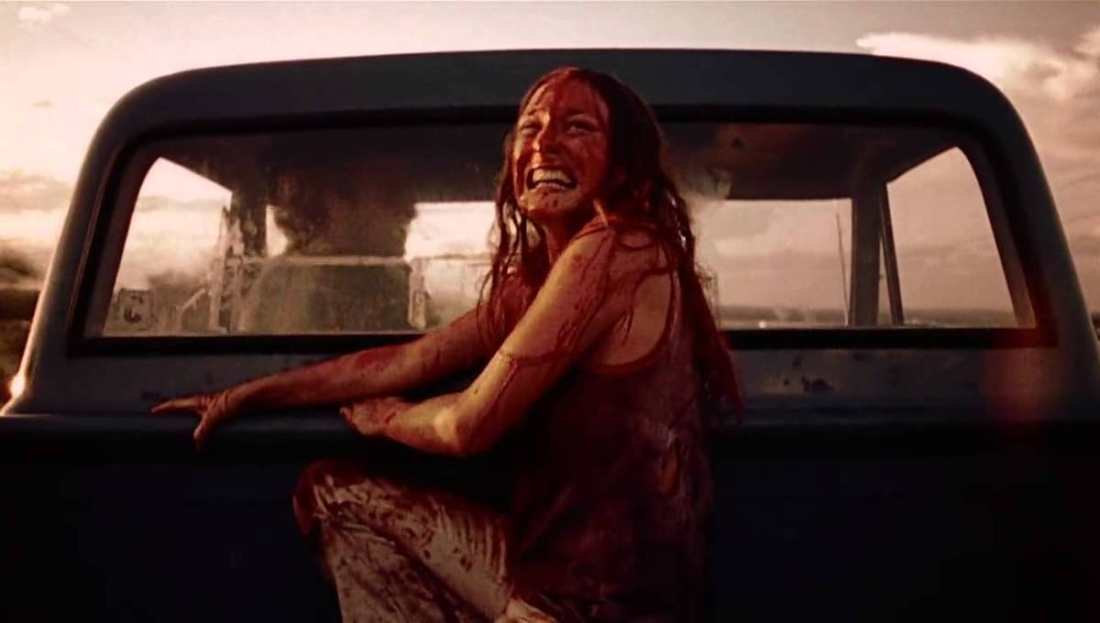 Image from the film Texas Chainsaw Massacre. A young woman, who is covered in blood, cries as she's driven away on the back of a pickup truck.