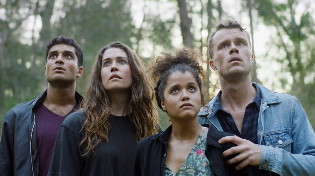 Image is from the film 'The Greenhouse' (2021). Four siblings stand side by side in a wooded area. They are all looking at something in the distance.