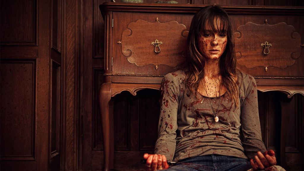 Sharni Vinson as Erin in You're Next (2001). Erin sits on the floor, leaning against a cabinet. She looks at her hands, which like the rest of her, are covered in splatters of blood.