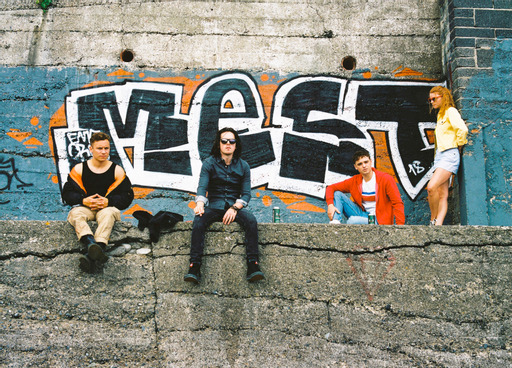 "Image is from the film 'Here Are the Young Men' (2021). Three young men sit on the top of a concrete wall, whilst a young woman stands next to them leaning her back against a blue wall. Behind them a brick wall is painted grey and blue, with ""mest"" written behind them in bold white and black graffiti lettering."
