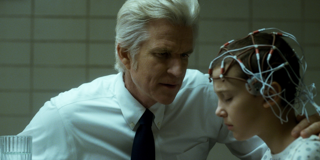 Dr Brenner talks to a young El, who has a series of wires places on her head. He is wearing a shirt and tie and has his hand on El's shoulder. In front of El is a glass of water.